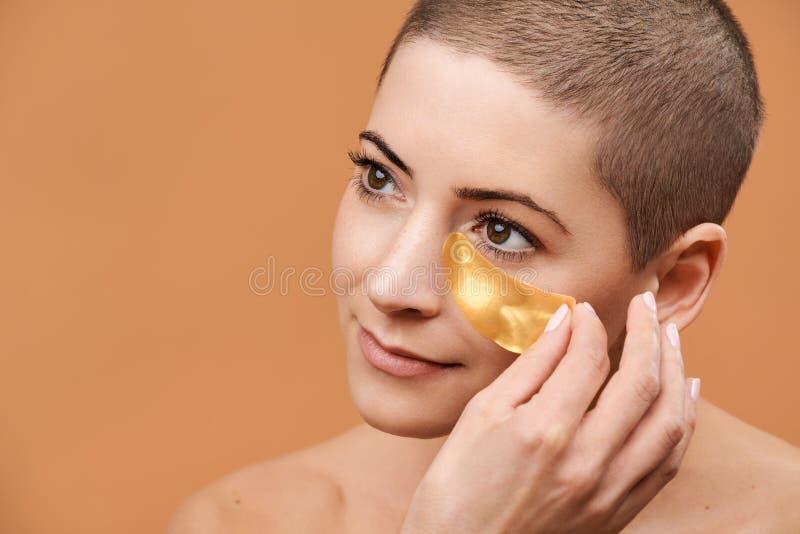 Le den mitt- 30-talkvinnan som applicerar den guld- collagenögonmaskeringen Foto av den attraktiva caucasian kvinnan med det raka arkivbild