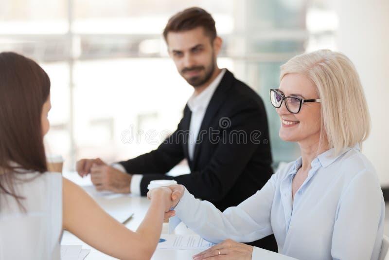 Le den mogna affärskvinnan som skakar handen av kollegan på möte royaltyfria foton