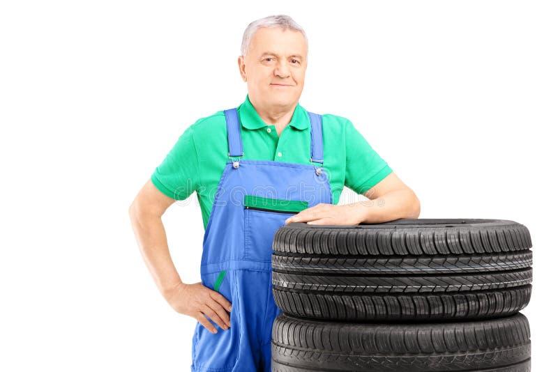Le den mogna arbetaren som poserar på bilgummihjul royaltyfria foton