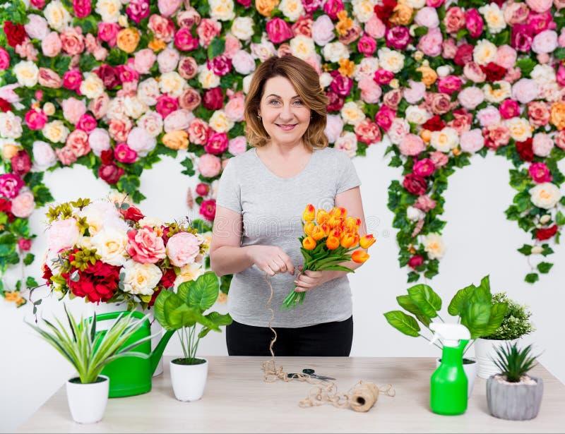 Le den mogna kvinnablomsterhandlaren eller trädgårdsmästaren som arbetar i blomsterhandel royaltyfria foton