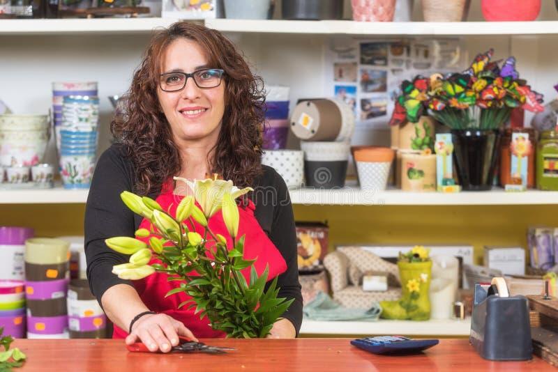 Le den mogna kvinnablomsterhandlaren som gör en bukett av blommor på blomsterhandeln royaltyfria foton