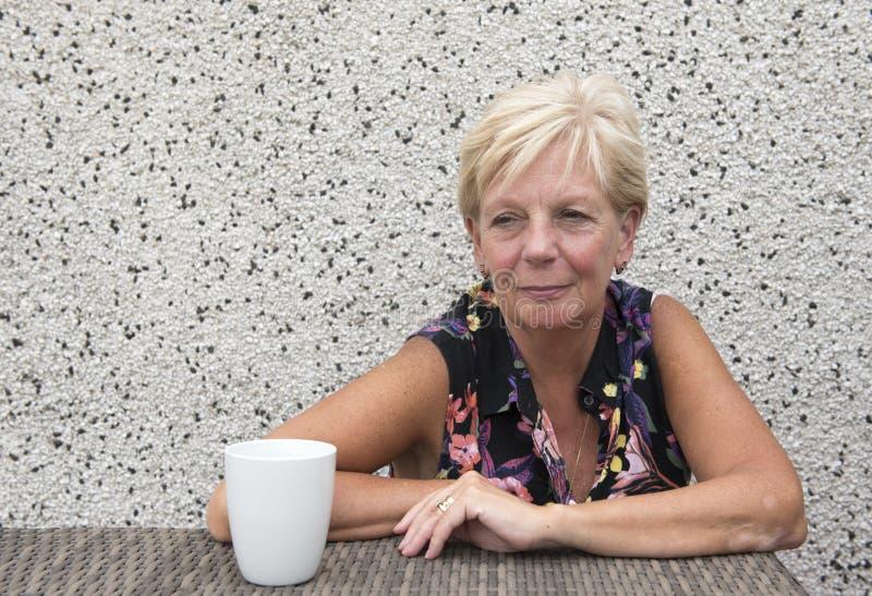Le den mogna kvinnan med kaffe med kopieringsutrymme arkivfoto