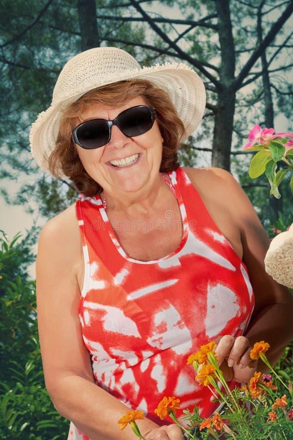 Le den mogna kvinnan som beskär blommor royaltyfri foto