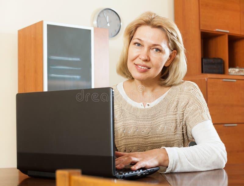 Le den mogna kvinnan som hemma använder bärbara datorn royaltyfria bilder