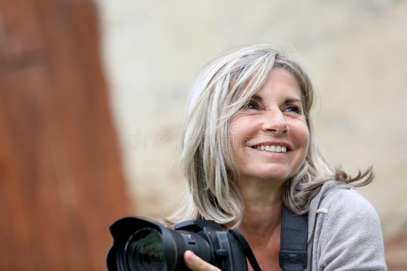Le den mogna kvinnan som rymmer en kamera royaltyfri fotografi