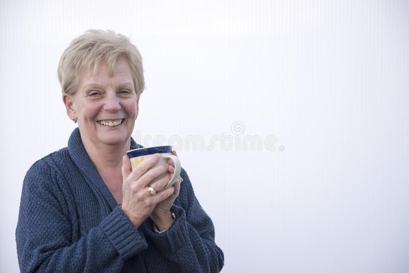 Le den mogna kvinnan som rymmer en kopp kaffe royaltyfria bilder