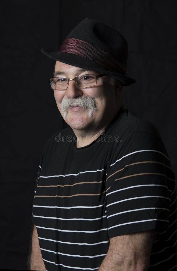 Le den mogna mannen med en hatt och exponeringsglas arkivbilder