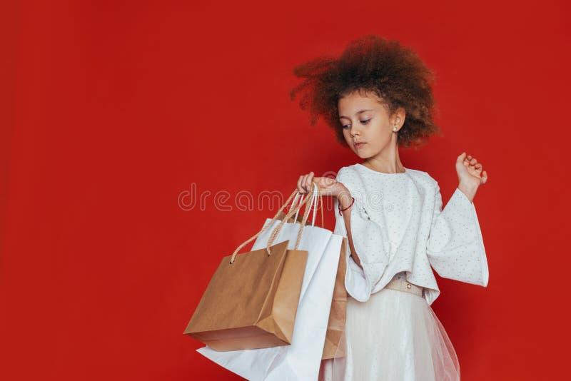 Le den nätta flickan med lockigt hår och shopping på en röd bakgrund arkivfoton