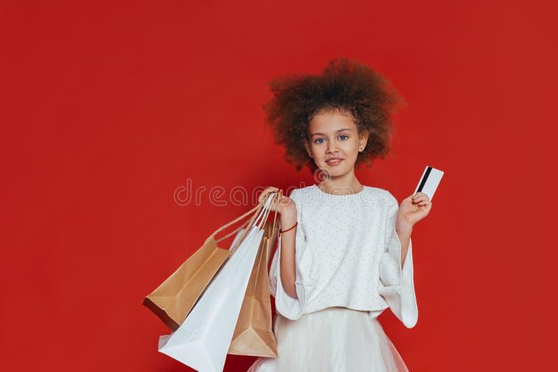 Le den nätta flickan med lockigt hår och shopping på en röd bakgrund royaltyfri foto