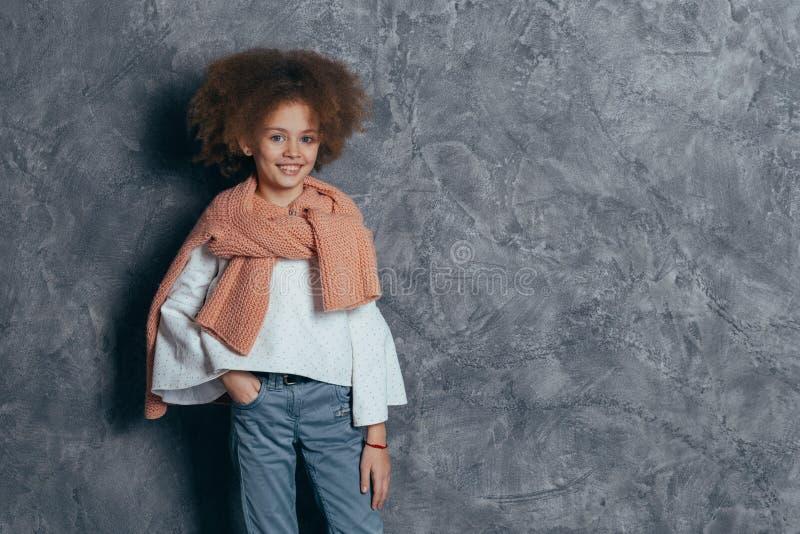 Le den nätta flickan med lockigt hår som står i studion på den gråa väggen fotografering för bildbyråer