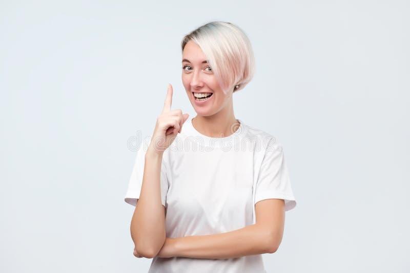 Le den nätta flickan som pekar pekfingret upp att ge rådgivning royaltyfria foton