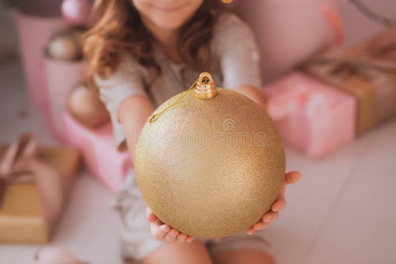 Le den nätta flickan som rymmer den enorma guld- feriebollen i händer royaltyfri foto
