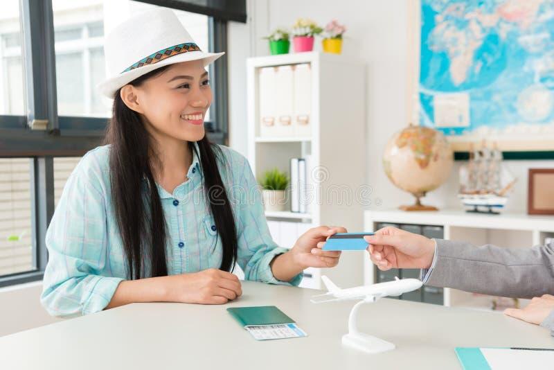 Le den nätta kvinnahandelsresanden som ger kreditkorten royaltyfri bild