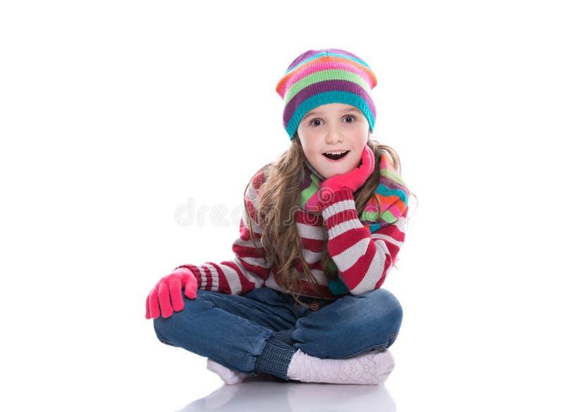 Le den nätta lilla flickan som bär den färgrika stack halsduken, hatten och handskar som isoleras på vit bakgrund Mode och skönhe fotografering för bildbyråer