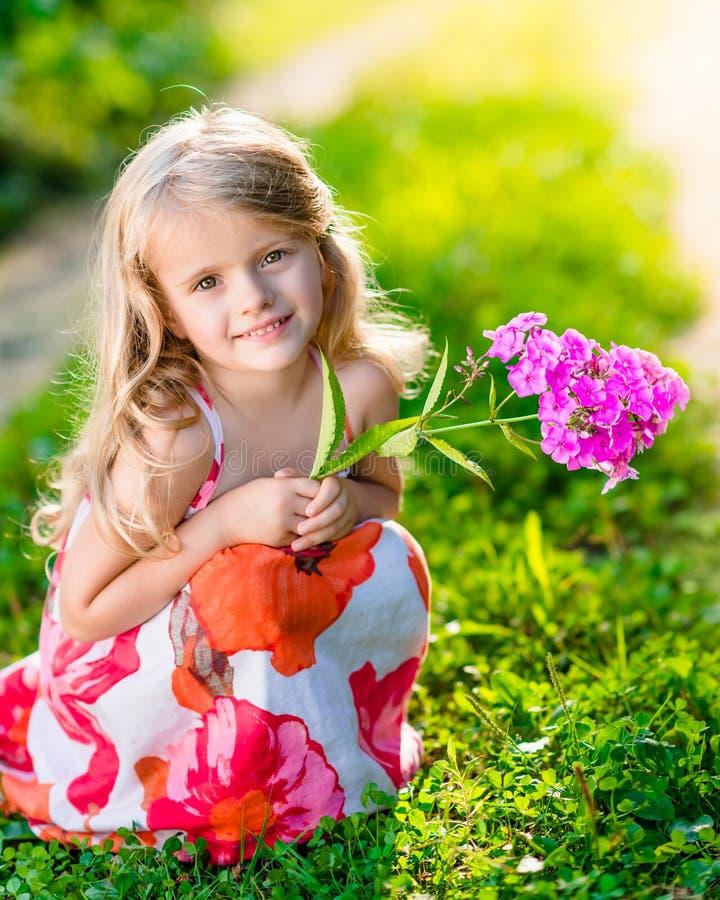 Le den nätta lilla flickan som squatting och rymmer lilor, blomma arkivfoto