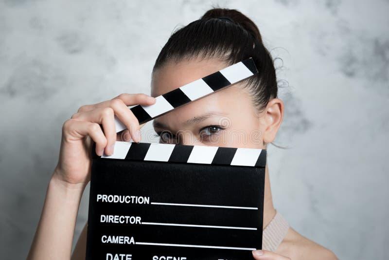 Le den nätta tonåriga kvinnan synar bak filmclapperen royaltyfria foton