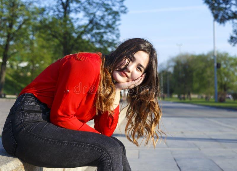 Le den nätta unga asiatiska kvinnan som sitter på stenbänk i stad, parkera arkivfoton