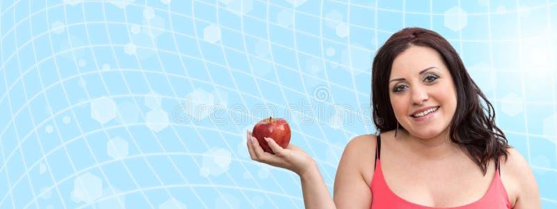 Le den nätta unga kvinnan som rymmer ett äpple royaltyfri foto