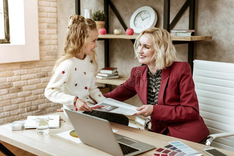 Le den nöjda blonda modern som har gyckel med hennes positiva dotter på arbete fotografering för bildbyråer