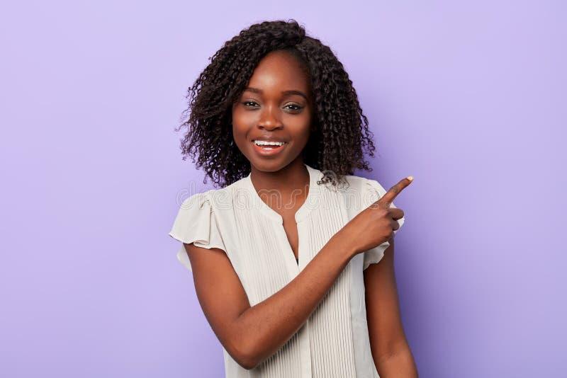 Le den positiva attraktiva afrikanska kvinnan som pekar på kopieringsutrymme fotografering för bildbyråer