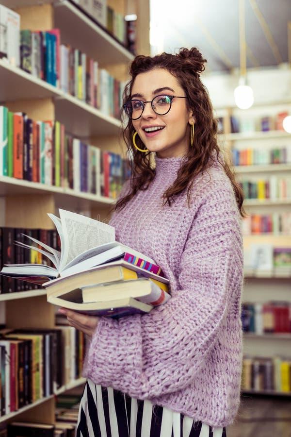 Le den positiva daminnehavbunten av böcker, medan resa till och med arkiv arkivfoto
