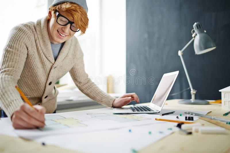 Le den röda Haired arkitekten Working på skrivbordet arkivbilder