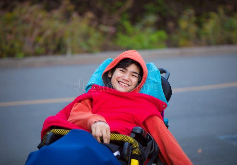 Le den rörelsehindrade pojken i rullstol utomhus på vägen fotografering för bildbyråer