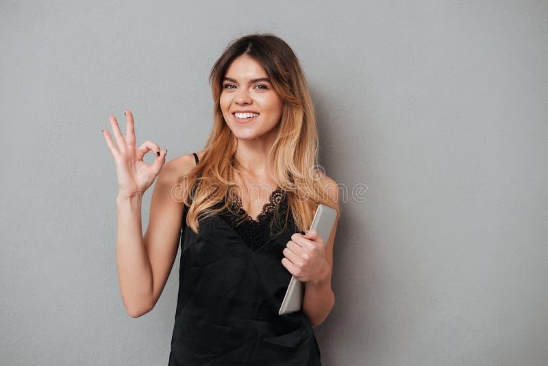 Le den säkra kvinnan som ok visar gest- och innehavminnestavladatoren royaltyfria foton