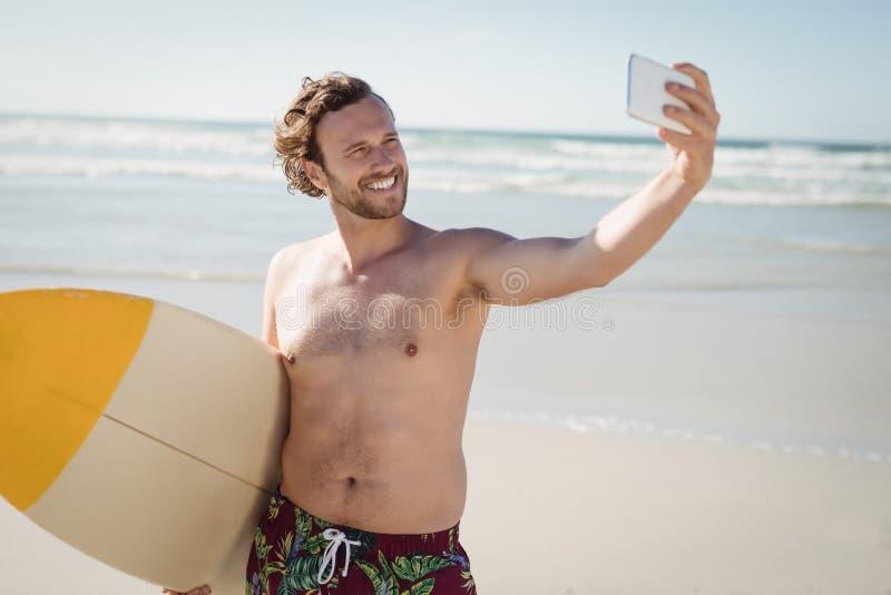 Le den shirtless mannen som tar selfie med surfingbrädan på stranden fotografering för bildbyråer