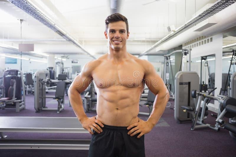 Le den shirtless muskulösa mannen med händer på höfter i idrottshall royaltyfri fotografi