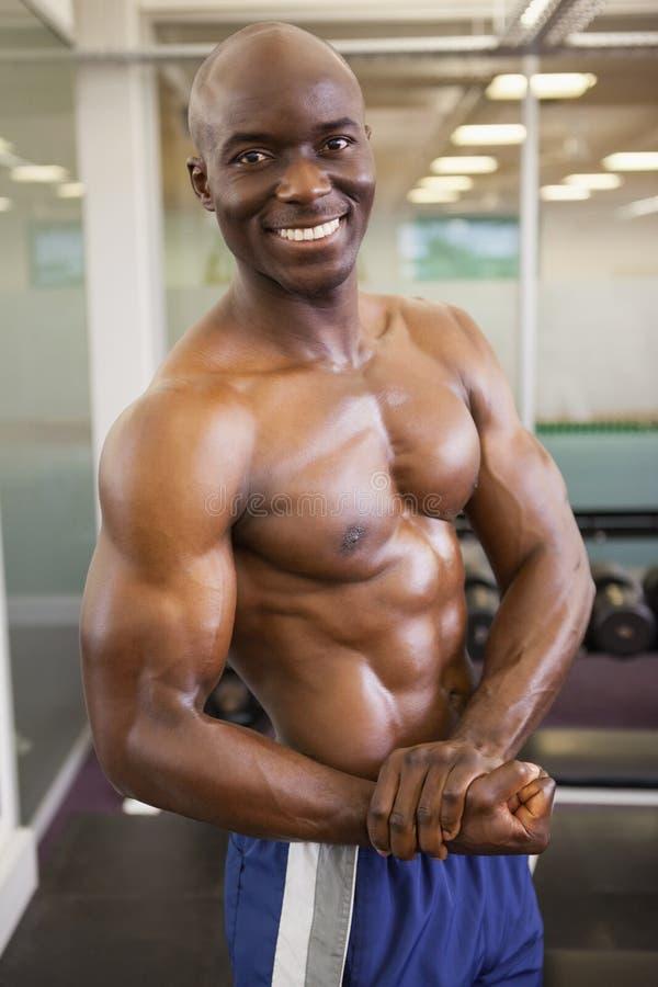 Le den shirtless muskulösa mannen som poserar i idrottshall royaltyfri bild