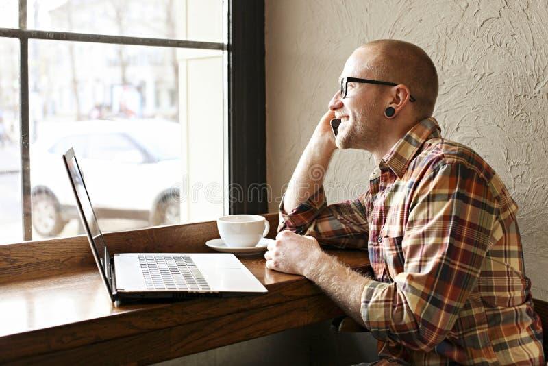 Le den skäggiga affärsmannen som bär tillfälliga hipsterkläder genom att använda bärbar dator- och cellsmartphonen i coffehus royaltyfri fotografi