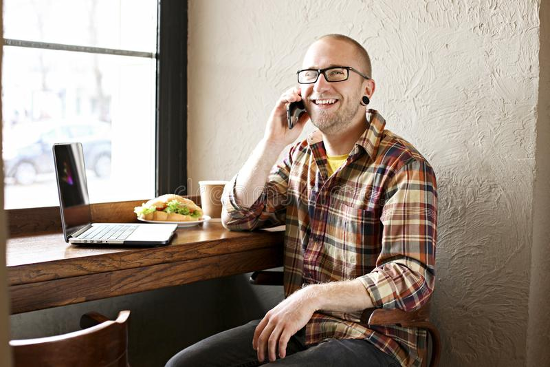 Le den skäggiga affärsmannen som bär tillfälliga hipsterkläder genom att använda bärbar dator- och cellsmartphonen i coffehus royaltyfria bilder
