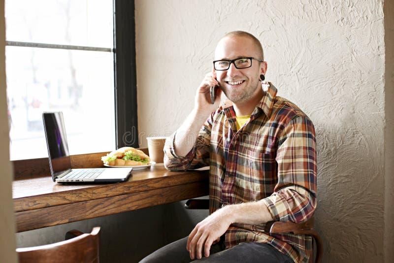 Le den skäggiga affärsmannen som bär tillfälliga hipsterkläder genom att använda bärbar dator- och cellsmartphonen i coffehus arkivbilder