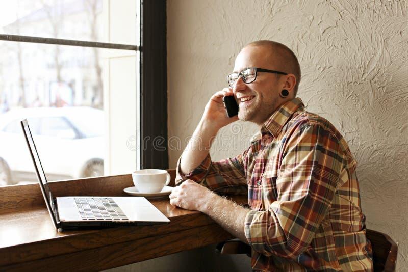 Le den skäggiga affärsmannen som bär tillfälliga hipsterkläder genom att använda bärbar dator- och cellsmartphonen i coffehus arkivfoto