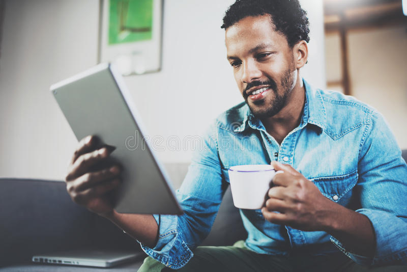 Le den skäggiga afrikanska mannen som använder minnestavlan för läs- morgonnyheterna och hemma dricker svart kaffe Begreppsfolk royaltyfri bild
