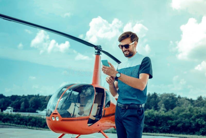 Le den snygga mannen i solglasögon som kontrollerar socialt massmedia royaltyfri bild