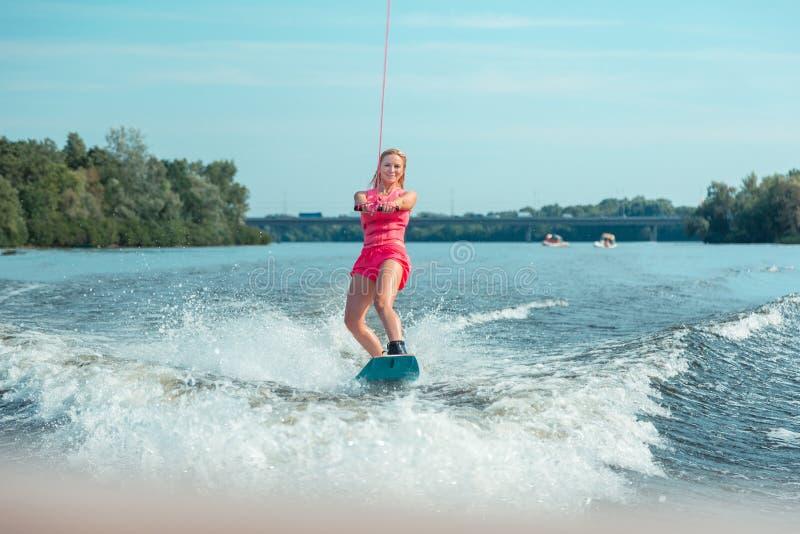 Le den sportiga färdiga blonda flickan som rider en wakeboard arkivbilder