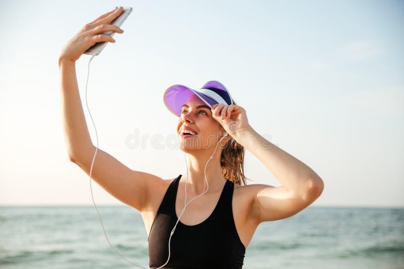 Le den sportiga kvinnan som tar selfie genom att använda smartphonen på stranden arkivfoto