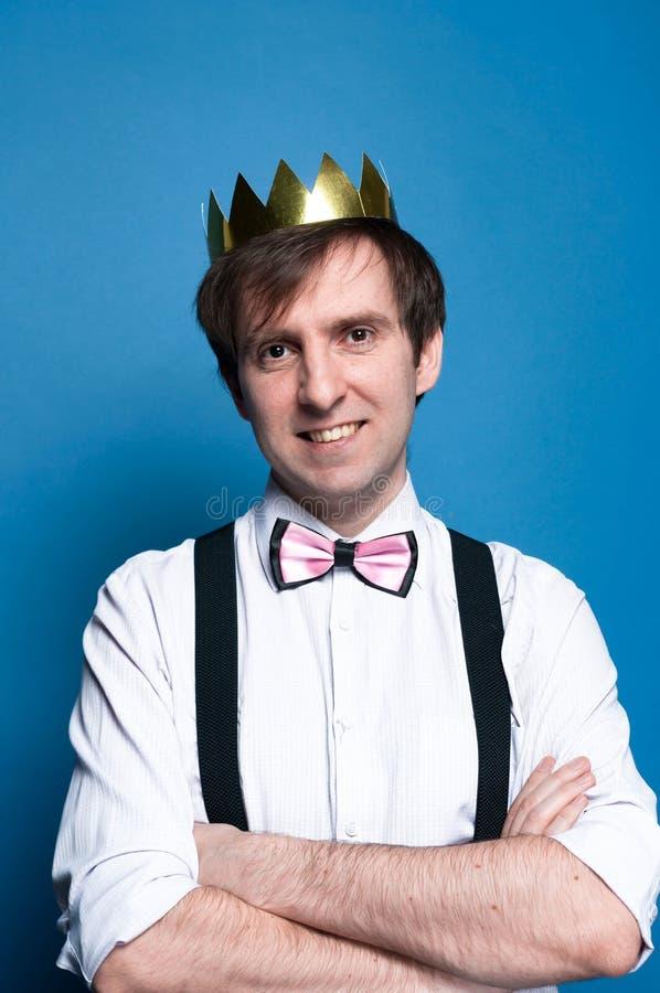 Le den stiliga mannen med mörkt hår i rosa skjorta med hoprullade muffar, flugan, suspenderen och den guld- skinande hemlagade kr arkivfoton