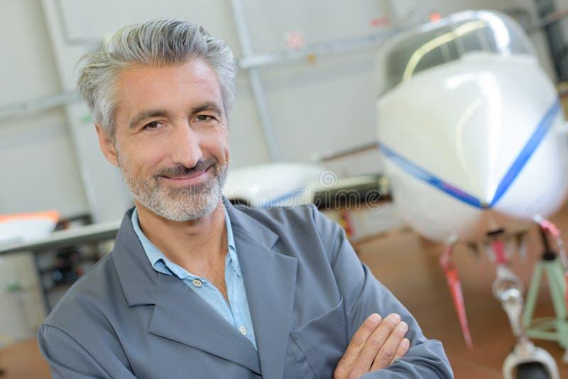 Le den stiliga piloten som poserar p? hangaren med motorflygplanet royaltyfria foton