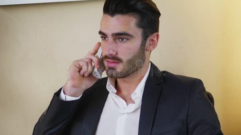 Le den stiliga unga affärsmannen på skrivbordet på telefonen arkivfoto