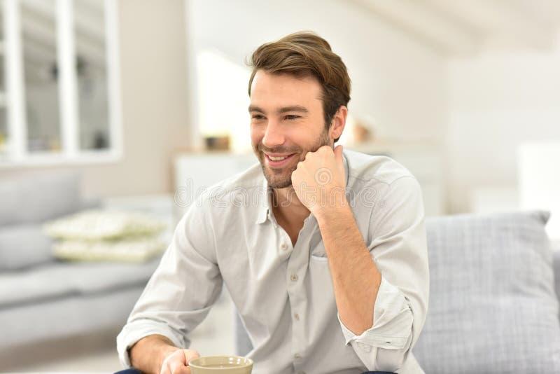 Le den stiliga unga mannen som hemma dricker kaffe royaltyfria bilder