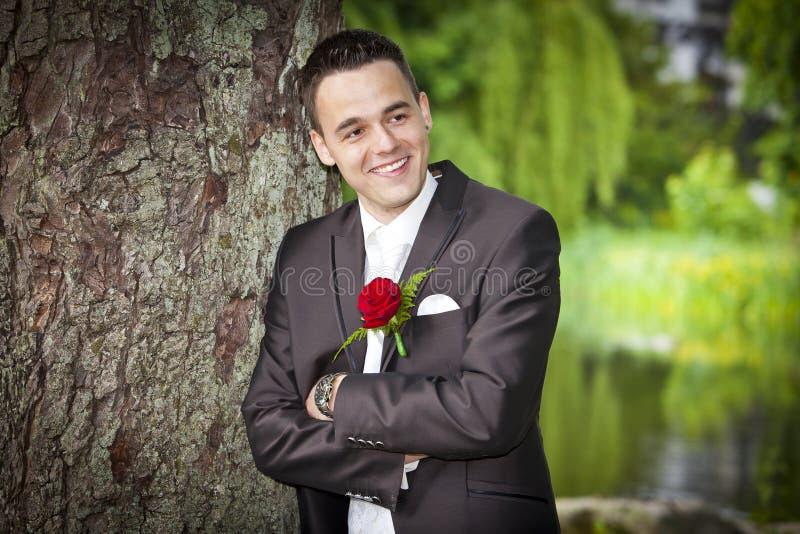 Le den stolta brudgummen - ung man i dräkt royaltyfri foto