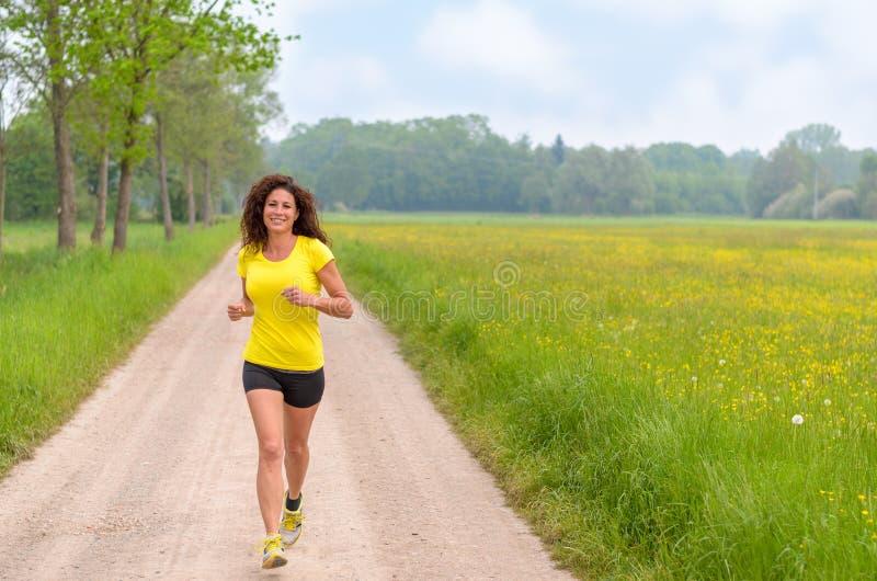 Le den sunda unga kvinnan som joggar i natur fotografering för bildbyråer