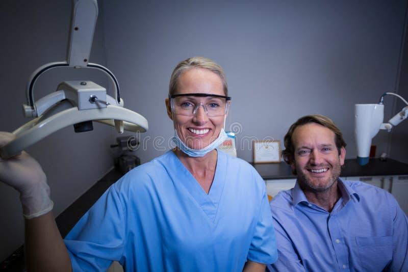 Le den tand- assistenten som justerar ljus i klinik royaltyfri bild