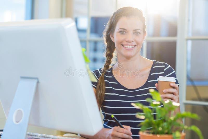 Le den tillfälliga affärskvinnan som arbetar på digitizer- och innehavkaffe arkivbild