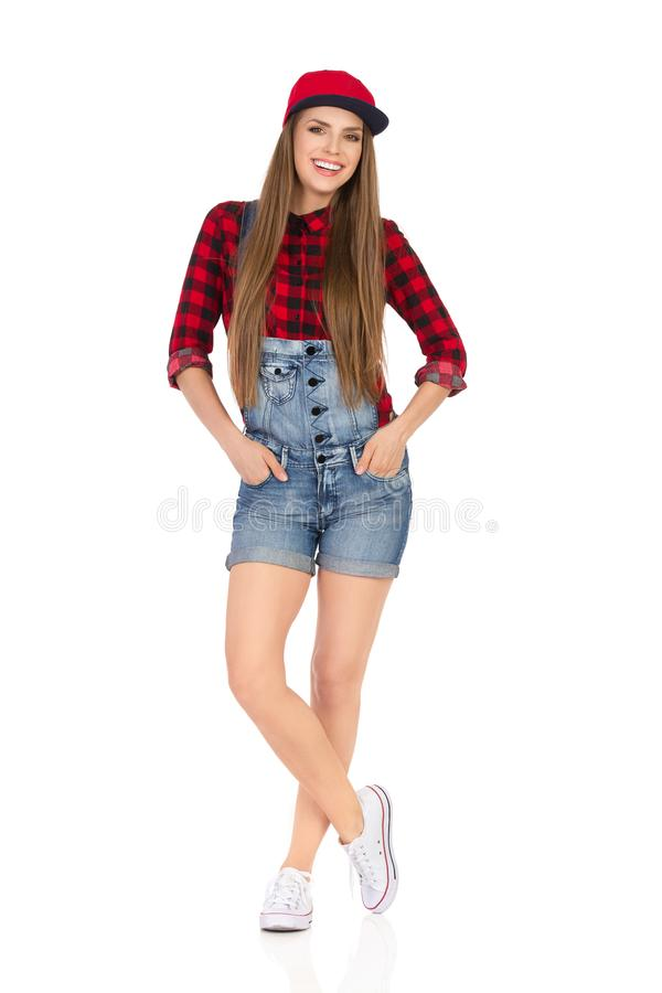 Le den tillfälliga unga kvinnan som poserar i rött fullt lock fotografering för bildbyråer