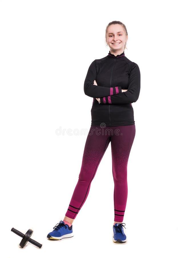 Le den tonåriga flickan i sportswear som utarbetar i studio på en vit bakgrund arkivbilder