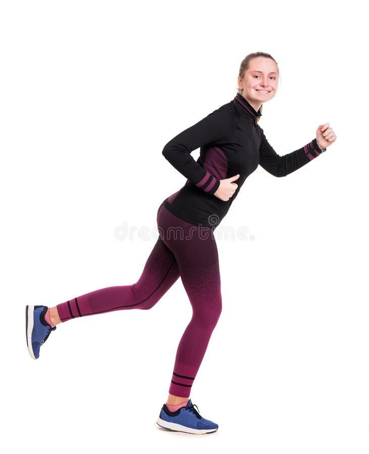Le den tonåriga flickan i sportswear som utarbetar i studio på en vit bakgrund arkivbild
